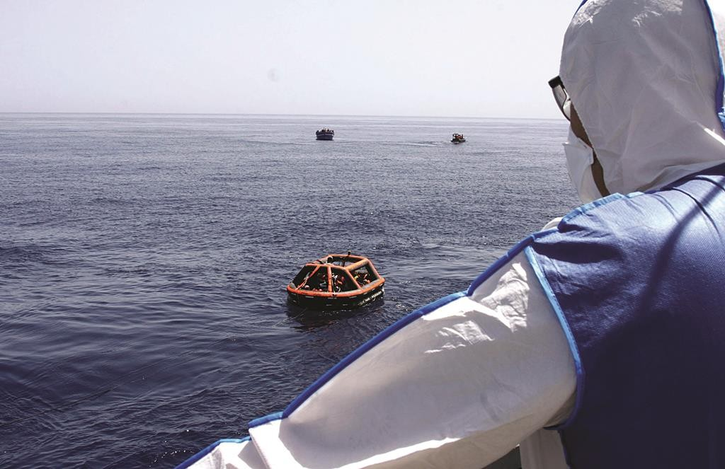 A German soldier wearing protective gear looking at float with rescued migrants during an operation on Friday, May 8, in the Mediterranean Sea.