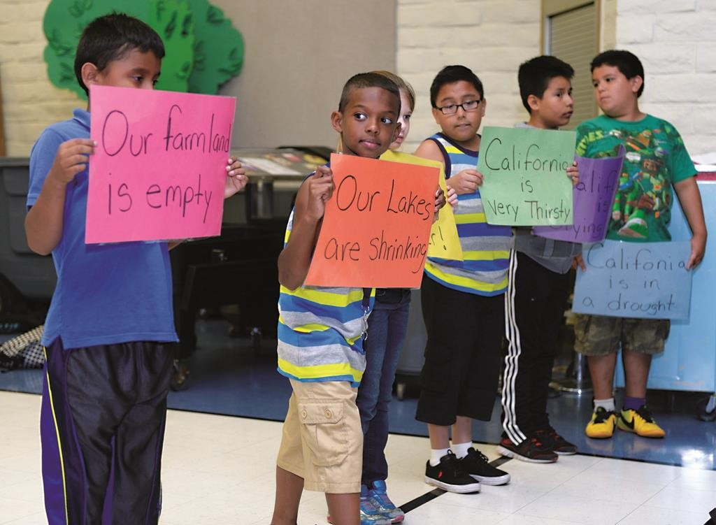 Third graders hold signs with others during a talent show rehearsal at Capistrano Elementary School's after-school program in Modesto, California. (Joan Barnett Lee/The Modesto Bee via AP)