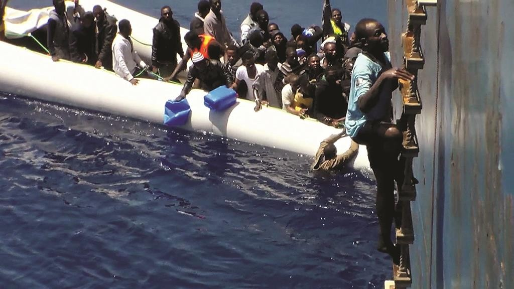 Dramatic footage emerged Tuesday, filmed by a crew member, showing a Mediterranean Sea rescue of migrants on a sinking rubber boat desperately clambering up ropes and a ladder of the cargo ship Zeran that came to their aid on May 3, 2015, in the sea between Libya and Sicily. (AP Photo)