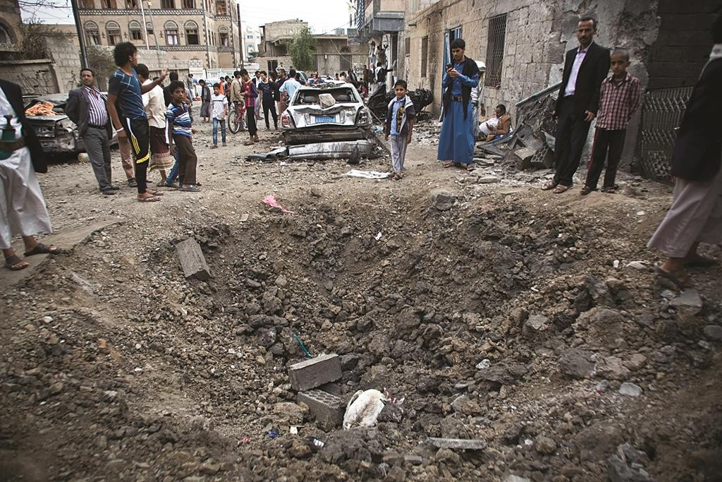 A crater left by a Saudi-led coalition air strike in Sanaa, Yemen, Wednesday.  (AP Photo/Hani Mohammed)
