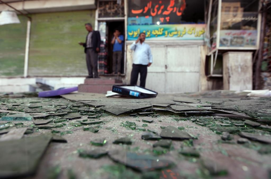 An Afghan shopkeeper speaks on a mobile phone after a suicide car bombing attack in Kabul, Afghanistan, Tuesday. (AP Photo/Rahmat Gul)