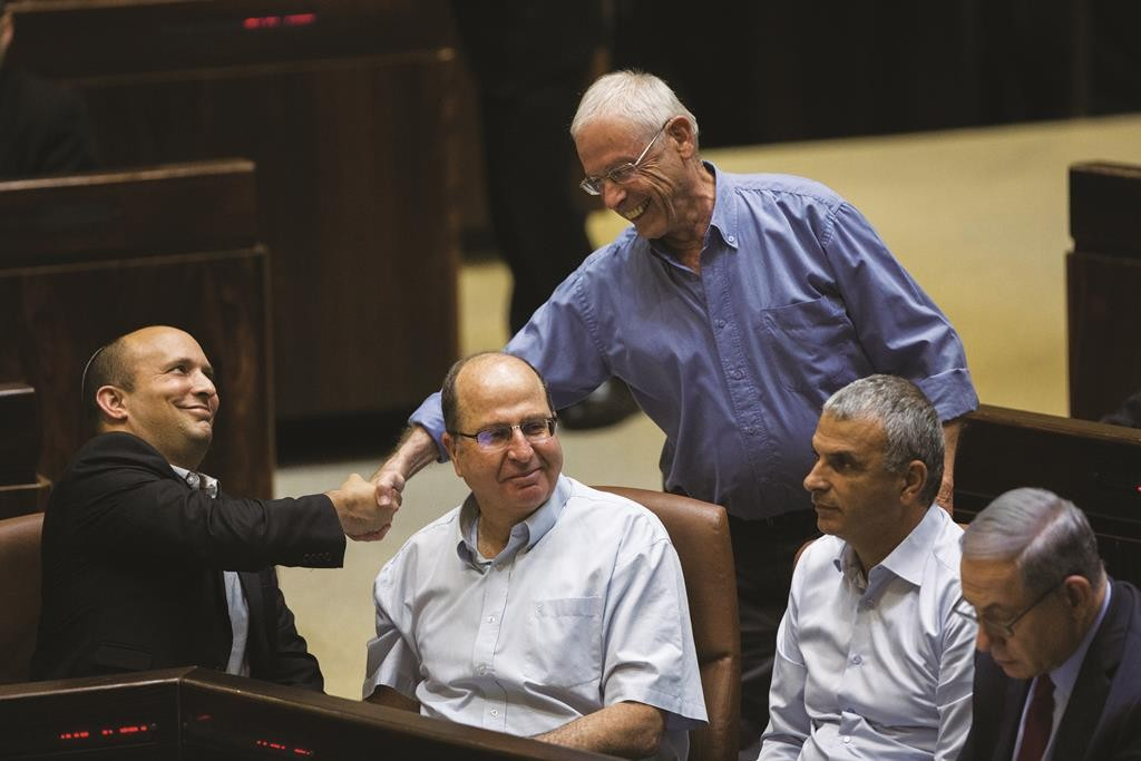 Grinning minister without portfolio Likud MK Benny Begin (standing), shaking hands with Education Minister Naftali Bennett in the Knesset, before Begin was asked to step aside for Gilad Erdan. (Yonatan Sindel/Flash90)