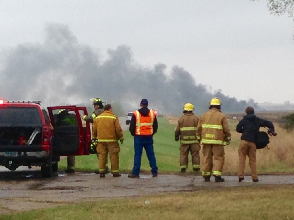 Emergency personnel watch as smoke rises in the background past a field after a BNSF Railway oil train derailed and caught fire in a rural area about two miles from Heimdal, N.D., on Wednesday, May 6, 2015. The central North Dakota town had to been evacuated due to the derailment and fire. (Tom Stromme/The Bismarck Tribune via AP)