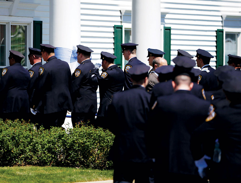 Police officers wait on Thursday to enter the wake for NYPD officer Brian Moore in Bethpage, N.Y. (AP Photo/Seth Wenig)
