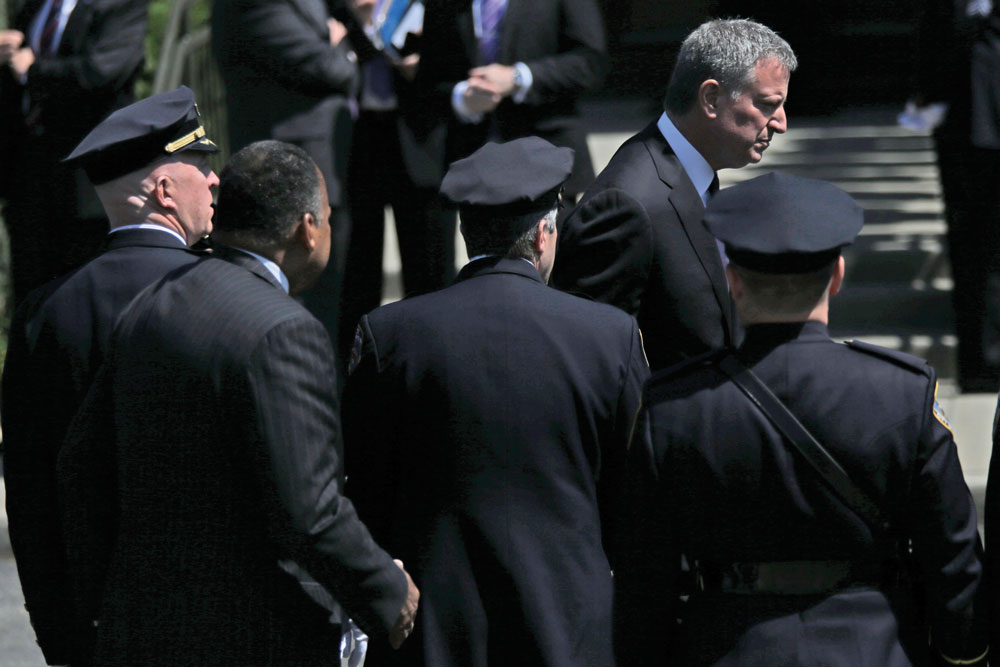 No Backs Turned This Time: Mayor Bill de Blasio (bottom) walks past Patrolmen's Benevolent Association president Patrick Lynch, second right, at the funeral. (Top) Officers salute as the procession for Officer Brian Moore passes in Seaford, N.Y. (AP Photo/Mary Altaffer)