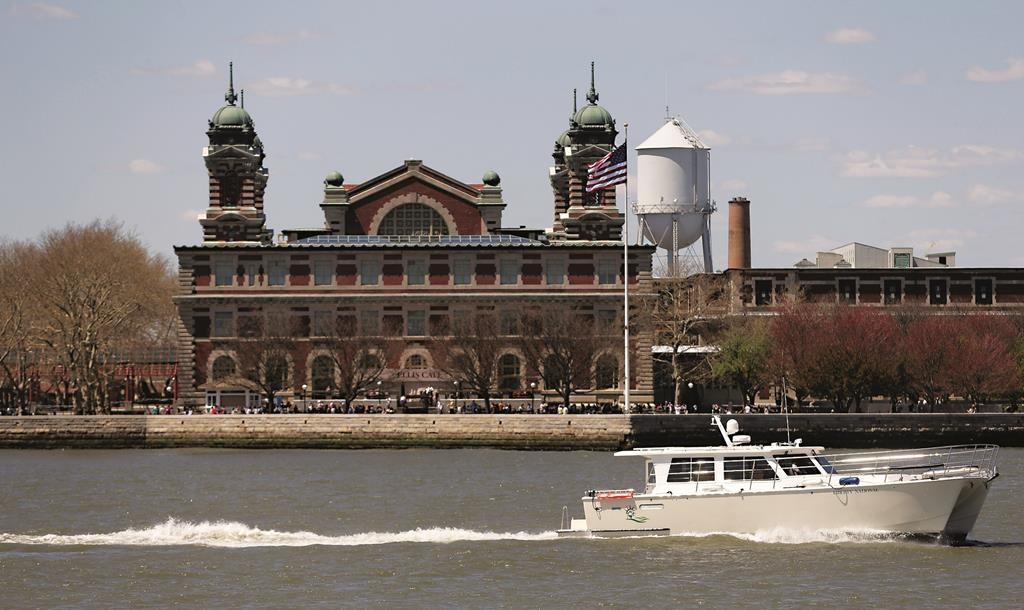 Windows at Ellis Island frame the Statue of Liberty (bottom) as a yacht makes its way through New York Harbor last week Wednesday. (AP Photo/Julie Jacobson)