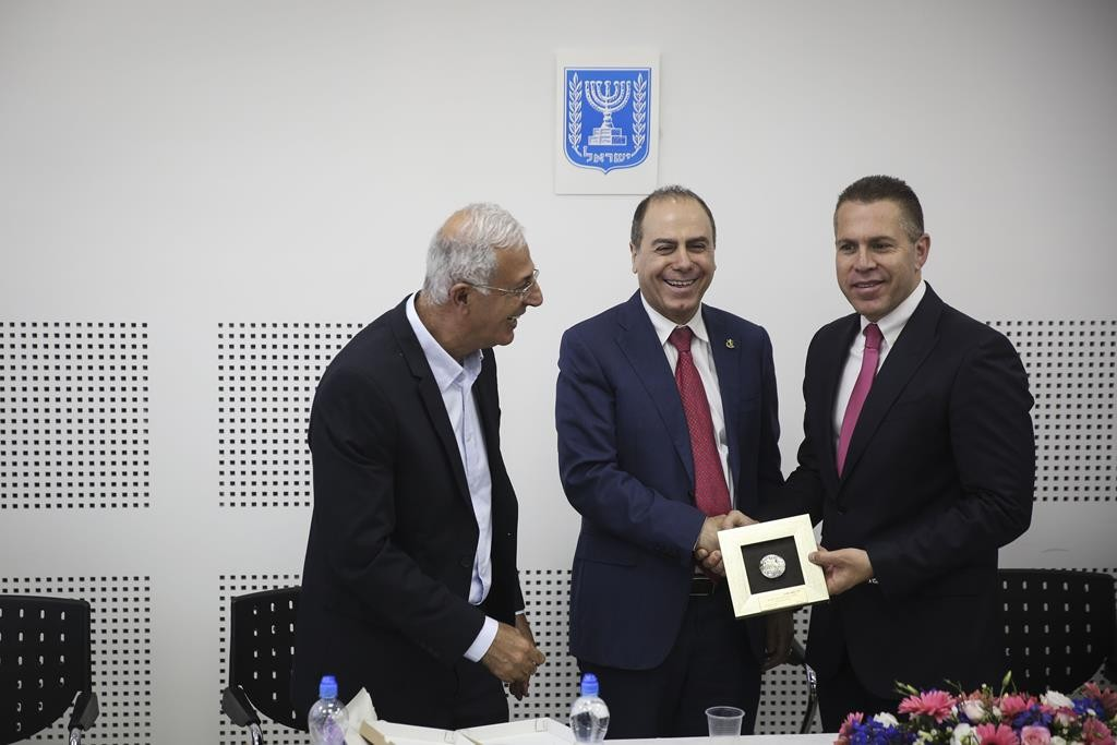 Newly appointed minister of Interior, Silvan Shalom (C-L) and outgoing minister Gilad Erdan(R) at a ceremony for replacing of minister, held at the Ministry of the Interior in Jerusalem. (Hadas Parush/Flash90)