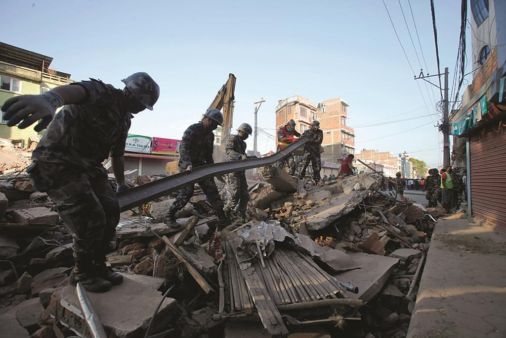 Nepalese security personnel remove an iron pillar from the debris of a building that collapsed in an earthquake in Kathmandu, Nepal, Tuesday. (AP Photo/Bikram Rai)