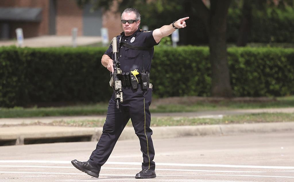 A Garland police officer directs traffic away from Naaman Forest High School and the Curtis Culwell Center after a fire alarm was sent at the high school, Tuesday, in Garland, Texas. (AP Photo/LM Otero )