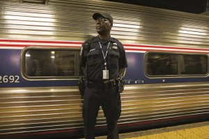 An Amtrak police officer stands guard outside Train 110, Monday, at Philadelphia's 30th Street Station.  (AP Photo/Michael R. Sisak)