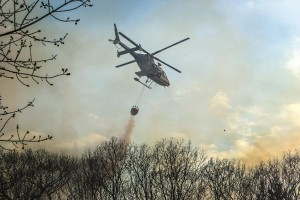 Firefighters on Monday set a backfire to burn up fuel so that the forest fire does not reach houses in Cragsmoor, N.Y., as a helicopter dumps water on a brush fire. (Allyse Pulliam/Times Herald-Record via AP)