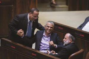 Moshe Kahlon (C) shares a light-hearted moment with Likud MK Ayoub Kara (L) and Shas MK Yitzhak Cohen in the Knesset on Monday. (Miriam Alster/Flash90)