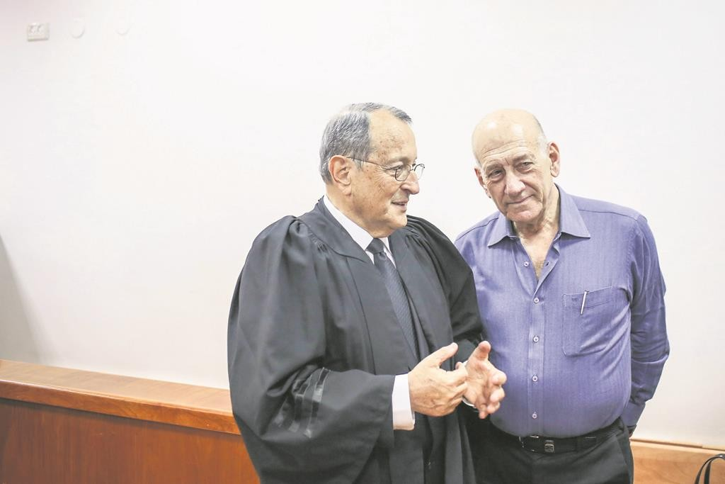 Former Prime Minister Ehud Olmert consults with his lawyer prior to the sentencing in Yerushalayim Monday.  (Noam Moskowitz/POOL/Flash90)