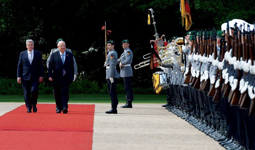 German President Joachim Gauck and Israeli President Reuven Rivlin walk past an honor guard as Rivlin arrives on Monday for a visit to Bellevue Palace in Berlin on the occasion of the 50th anniversary of the establishment of diplomatic relations between Germany and Israel. (Amos Ben Gershon / GPO)