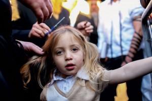 A three-year old boy receives his first haircut, called a chalakah, at Meron on Lag BaOmer. (Meir Vaknin/Flash90)