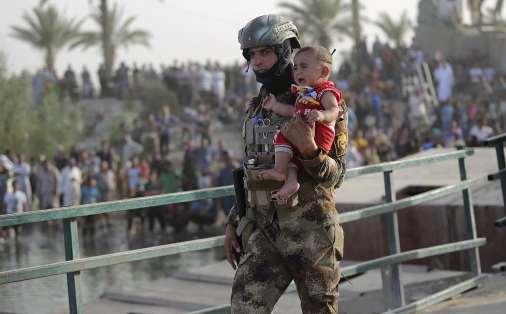 An Iraqi soldier carries a displaced child from Ramadi on the outskirts of Baghdad, Iraq. (REUTERS/Stringer)