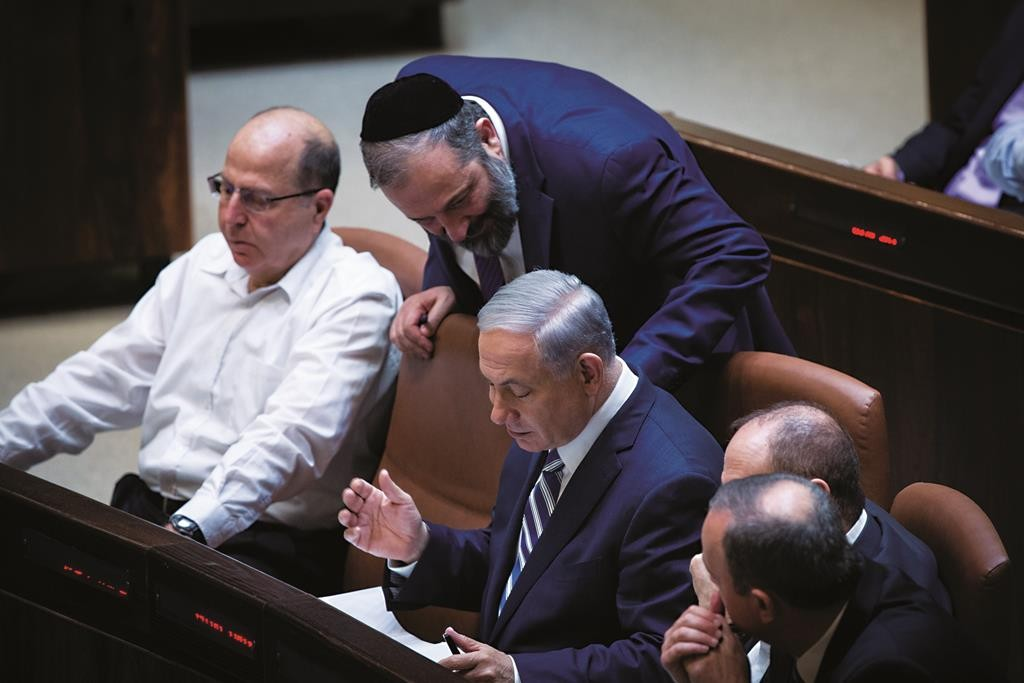 Israeli prime minister Benjamin Netanyahu speaks with leader of the ultra orthodox Jewish Shas party, Aryeh Deri, during a plenum session in the Israeli parliament on May 4, 2015. Photo by Miriam Alster/Flash90
