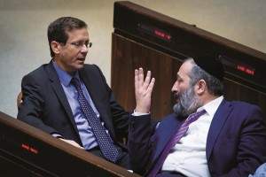 Shas chairman Aryeh Deri (R) with leader of the Zionist Camp party Isaac Herzog at the first day of the new Knesset on Monday. Deri invited Herzog to join the coalition. (Miriam Alster/Flash90)