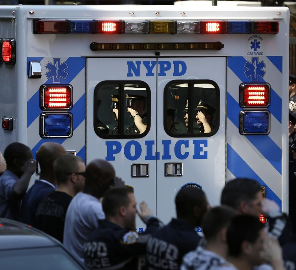New York City police officers salute as an ambulance carrying the body of officer Brian Moore leaves Jamaica Hospital in New York, May 4. The 25-year-old, shot in the head on Saturday as he tried to question a man sought on gun charges, died on Monday of his wounds. (AP PHOTO/Seth Wenig)