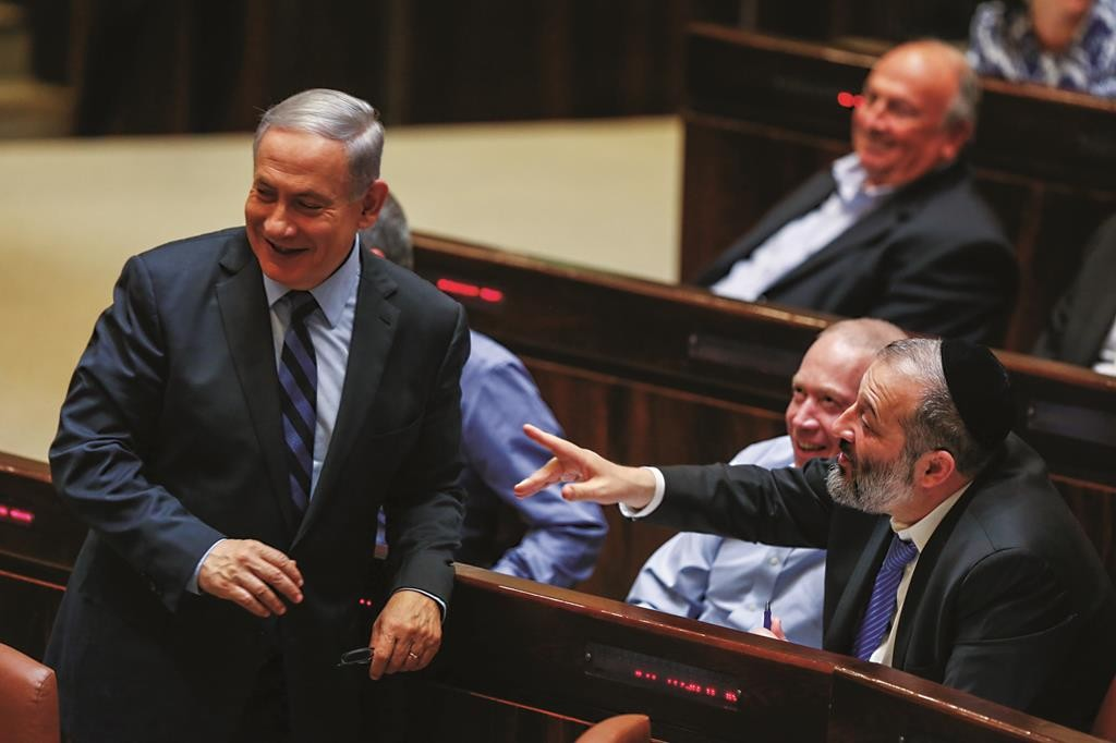 Prime Minister Binyamin Netanyahu (L) and Shas leader Aryeh Deri (R) in an expansive mood in the Knesset on Wednesday, as the bill for more ministers passed 61–59. (Hadas Parush/Flash90)