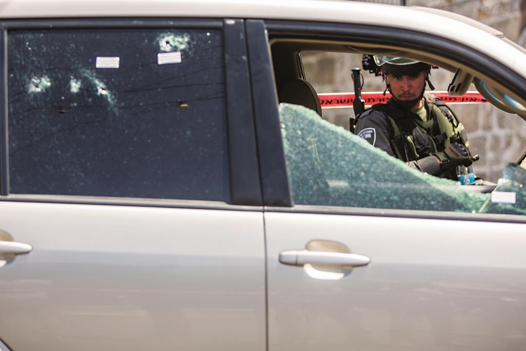 An Israeli policeman looks at the car used by a Palestinian terrorist on Wednesday to ram two of his fellow officers. (Yonatan Sindel/Flash90)