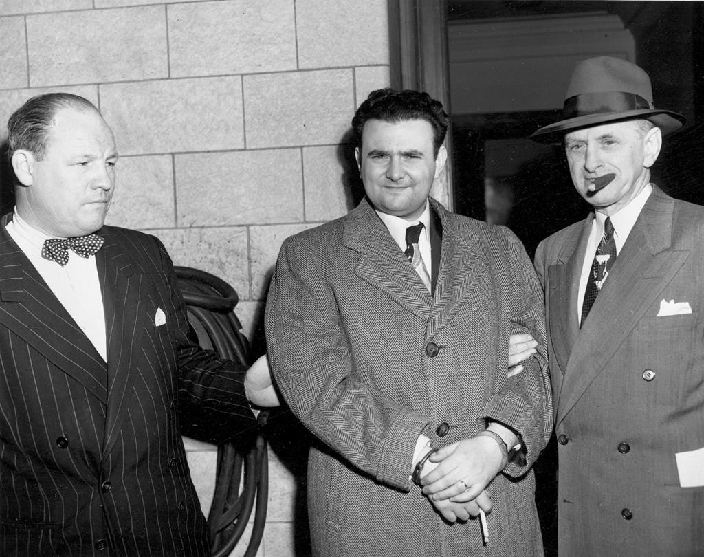 A handcuffed David Greenglass is escorted on April 6, 1951, by U.S. marshals from Federal Courthouse in New York after being sentenced to 15 years in prison. (AP Photo)