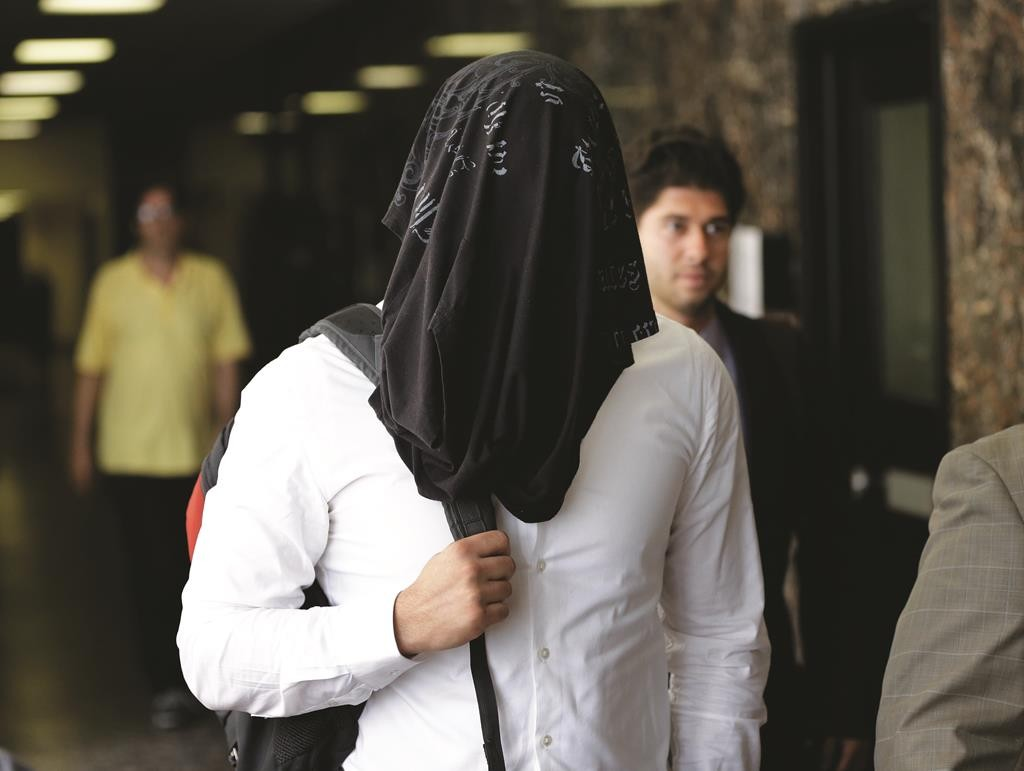 NYPD detective Wojciech Braszczok covers his face as he leaves a Manhattan courtroom last Tuesday. (AP Photo/Seth Wenig)