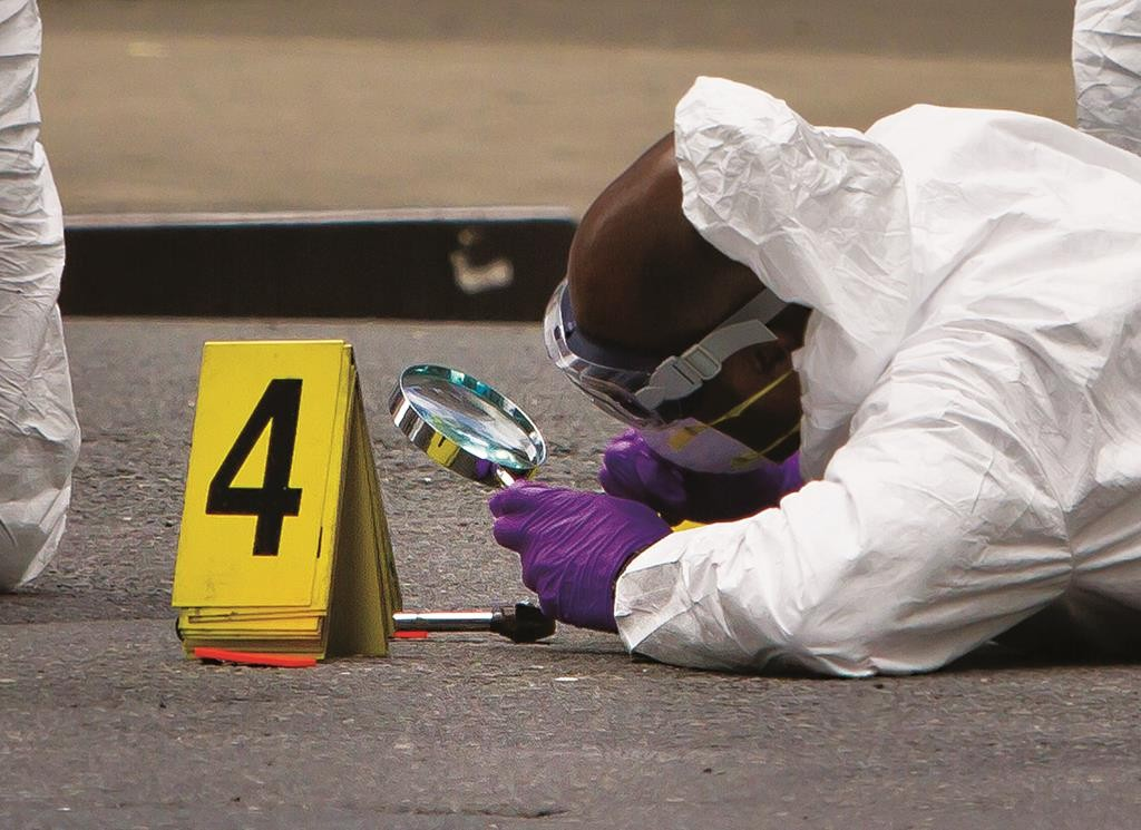 An NYPD investigator examines a hammer used to attack an officer in Manhattan. (AP Photo/Bebeto Matthews)
