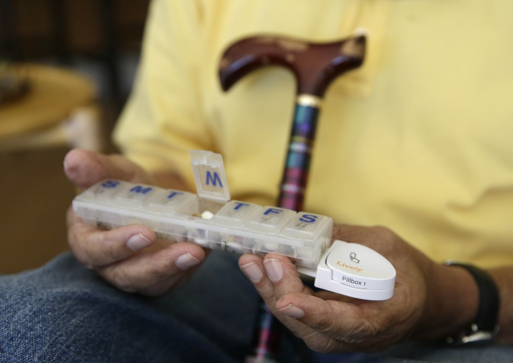 81-year-old Bill Dworsky holds his pill container with a motion sensor attached at his home in San Francisco. Each time Bill or his 80-year-old wife, Dorothy, opens the refrigerator, uses the oven, closes the bathroom door or lifts the lid on a pill container, tiny sensors in their home make notes on a digital logbook, which their son Phil Dworsky monitors daily on his smartphone. (AP Photo/Eric Risberg)