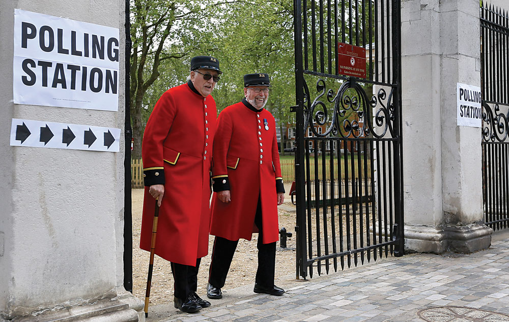 Chelsea pensioners smile as they see the media after voting at a polling station in London, Thursday. (AP Photo/Kirsty Wigglesworth)