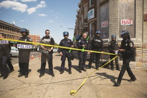 An officer rolls out police tape as other officers form a line to block North Ave., May 4, 2015. (Allison Shelley/Getty Images)
