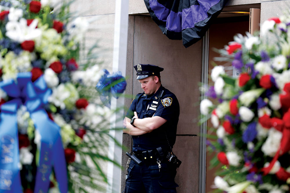 A police officer on Tuesday stands in front of Officer Brian Moore's precinct in Queens. (AP Photo/Seth Wenig)