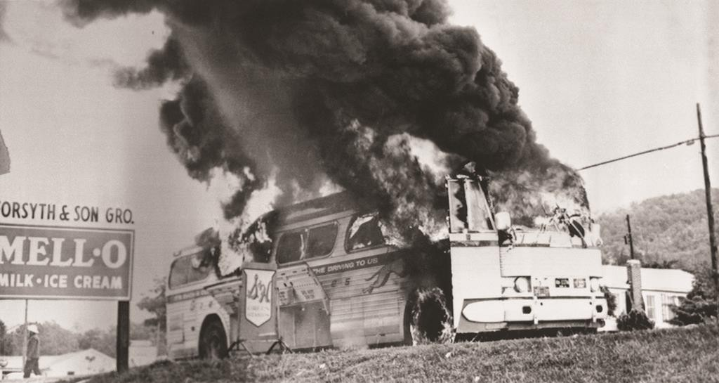A Freedom Rider bus went up in flames in May 1961 when a fire bomb was tossed through a window near Anniston, Ala. The bus, which was testing bus station segregation in the south, had stopped because of a flat tire. Passengers escaped without serious injury. (AP Photo)