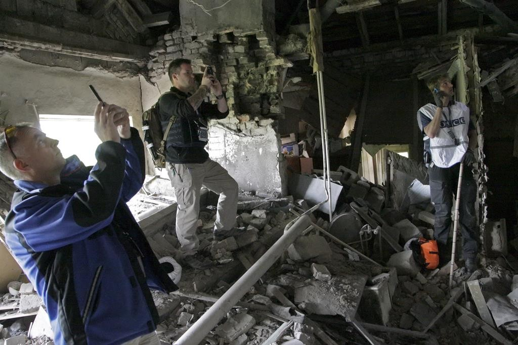 Members of the Organization for Security and Co-operation in Europe (OSCE) work within the ruins of a residential building, which, according to locals, was recently damaged by shelling, in Donetsk, Ukraine, Tuesday. (REUTERS/Alexander Ermochenko)