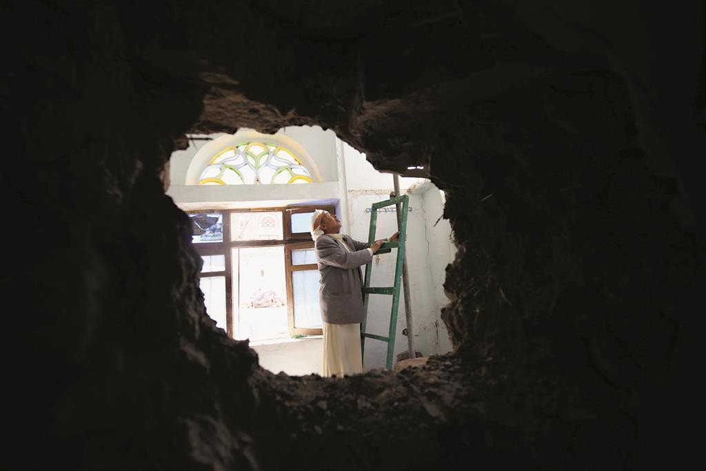 A man looks at his home, which was damaged by a shell that landed from an army weapons depot after the depot was hit by an air strike, in old Sanaa city Tuesday. (REUTERS/Mohamed al-Sayaghi)