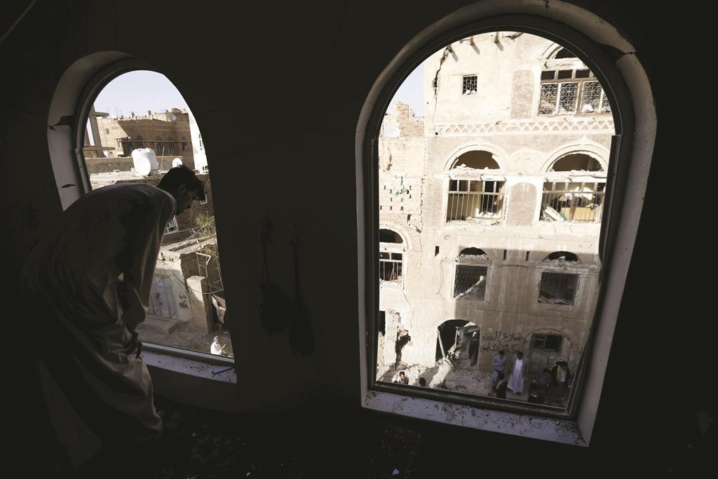 A man looks at damage outside his house caused by a car bomb attack in Sanaa Tuesday. A car bomb claimed by Islamic State exploded in the Yemeni capital overnight, medics said, wounding at least 28 people gathered to mourn another attack earlier this month. (REUTERS/Khaled Abdullah)