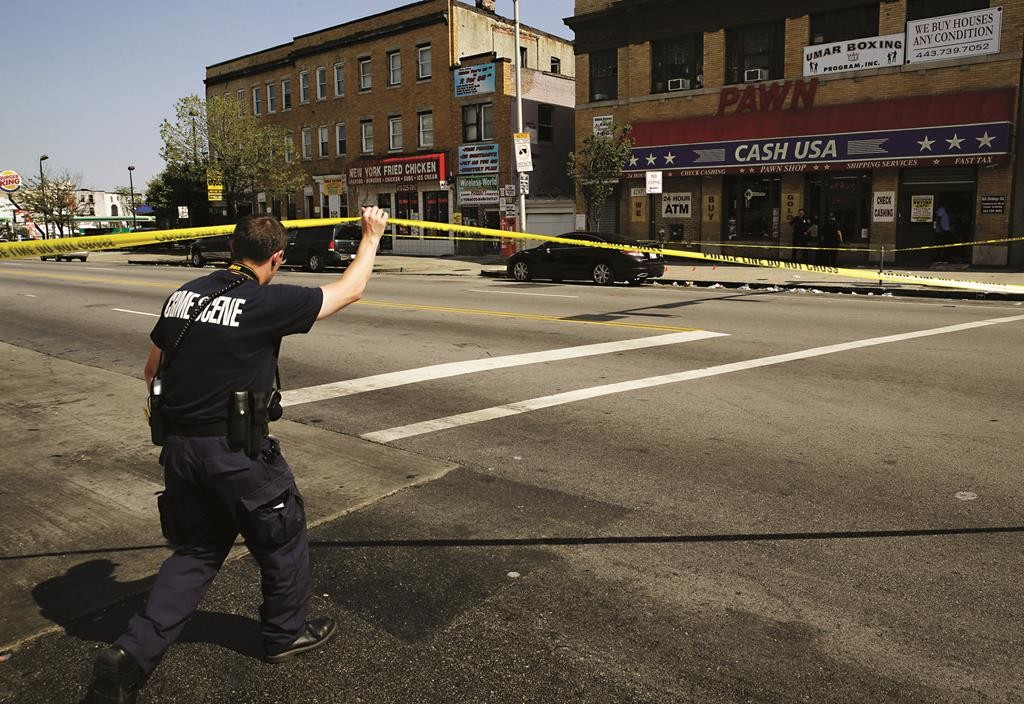 A police crime scene technician heads in to document evidence at the scene of a shooting at the intersection of West North Avenue and Druid Hill Avenue in West Baltimore, Maryland, Sunday. (REUTERS/Jim Bourg)