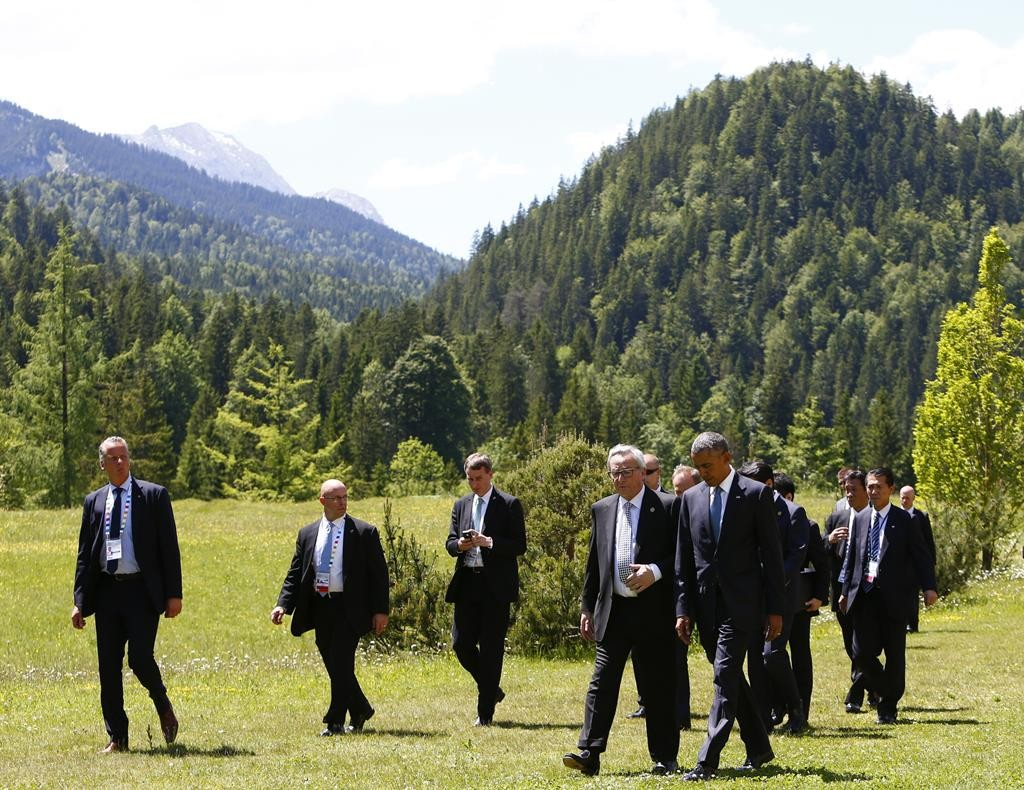 European Commission President Jean-Claude Juncker (center L) and President Barack Obama walk to attend their first meeting in the hotel castle Elmau in Kruen, Germany, on Sunday. (REUTERS/Michaela Rehle)