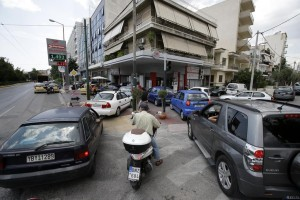 Drivers wait to fill cars and scooters at a gas station in Athens, Monday. Anxious Greeks lined up at ATMs as they gradually began dispensing cash again on the first day of capital controls imposed in a dramatic twist in Greece's five-year financial saga.  (AP Photo/Thanassis Stavrakis)