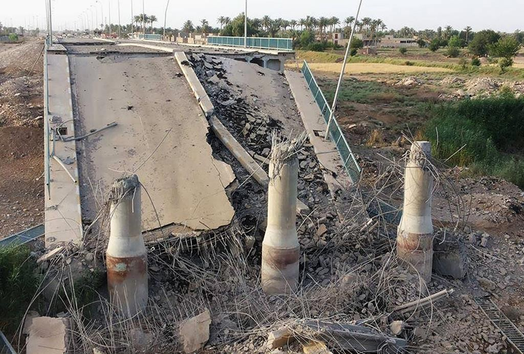 This photo taken Wednesday, June 3, shows a destroyed bridge on the Euphrates river in northern Ramadi, Iraq. The Islamic State group destroyed the bridge with a car bomb to cut the northern entrance to the city, locals said. (AP Photo)