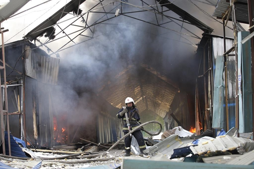 A firefighter extinguishes a fire at a market destroyed after shelling in Donetsk, Ukraine, Wednesday, during battles on Wednesday in eastern Ukraine territories. (AP Photo/Alexander Ermochenko)