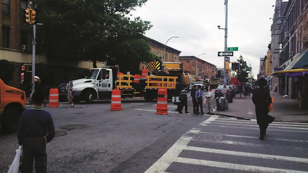 Transportation workers on Wednesday morning repave Boro Park's 14th Avenue and 45th Street. (News Breakers)
