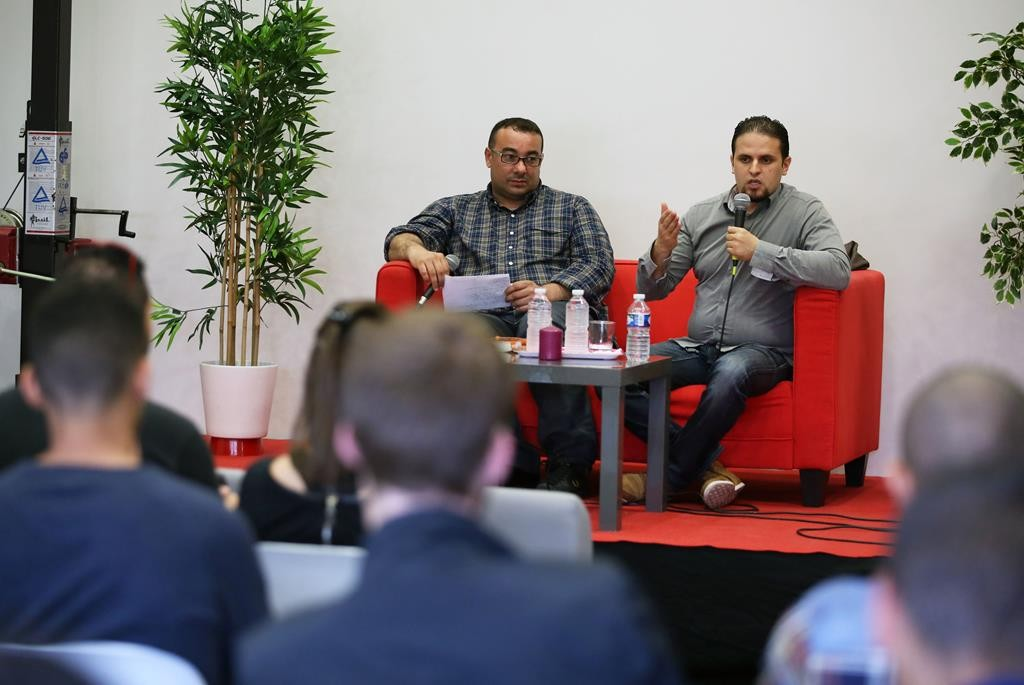 In this May 13 photo, former Guantanamo detainee and al-Qaida trainee Mourad Benchellali, seated on stage at right, addresses the audience, during a conference, in Gennevilliers, suburban Paris, France. (AP Photo/Remy de la Mauviniere)