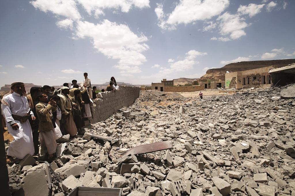 People look on, near the site of a building destroyed by a Saudi-led air strike near Sanaa. (REUTERS/Mohamed al-Sayaghi)
