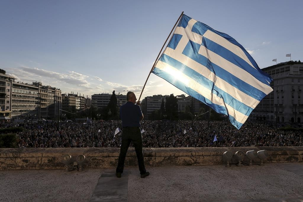 A man waves a Greek national flag at the premises of the parliament building during a rally that called on Greece's government to clinch a deal with its international creditors  and secure Greece's future in the Eurozone, in Athens, Greece, Monday.  (REUTERS/Yiannis Liakos/Intimenews)
