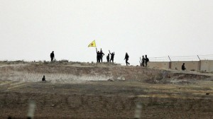 This photo, taken from the Turkish side of the border between Turkey and Syria, shows Kurdish fighters with the Kurdish People's Protection Units, or YPG, Monday. (AP Photo/Lefteris Pitarakis)
