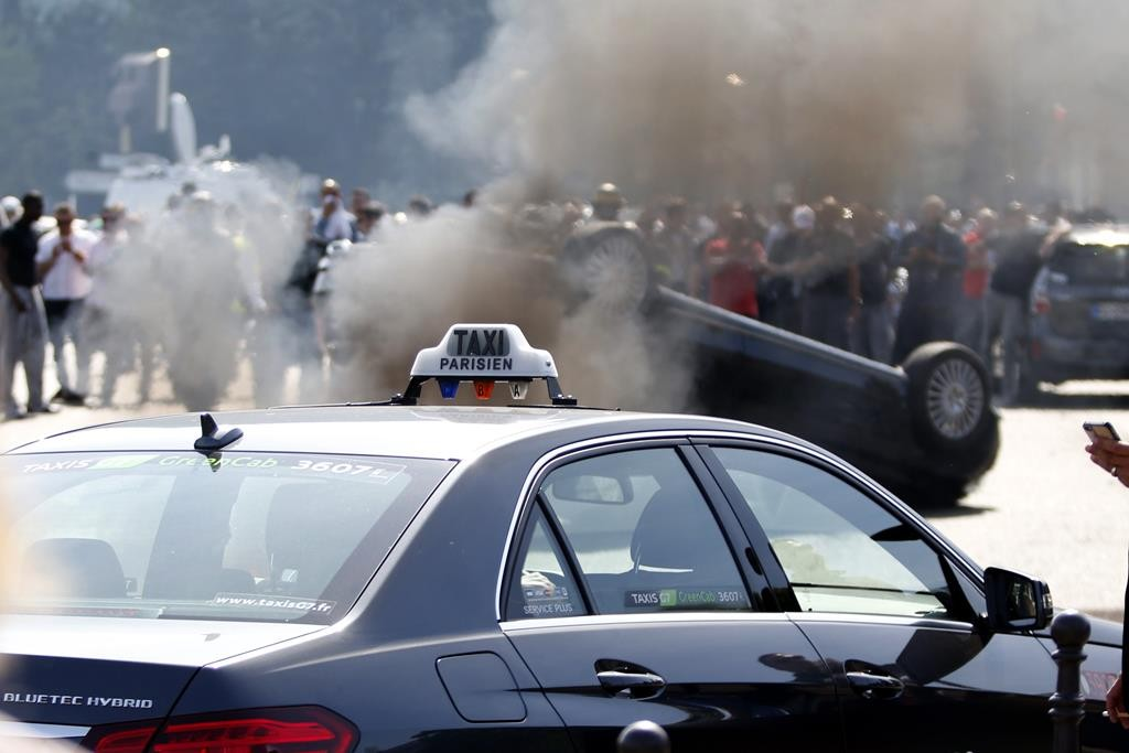 An overturned car is pictured as French taxi drivers, who are on strike, demonstrate at Porte Maillot to block the traffic on the Paris ring road during a national protest against car-sharing service Uber, in Paris, France, Thursday.  (REUTERS/Charles Platiau)
