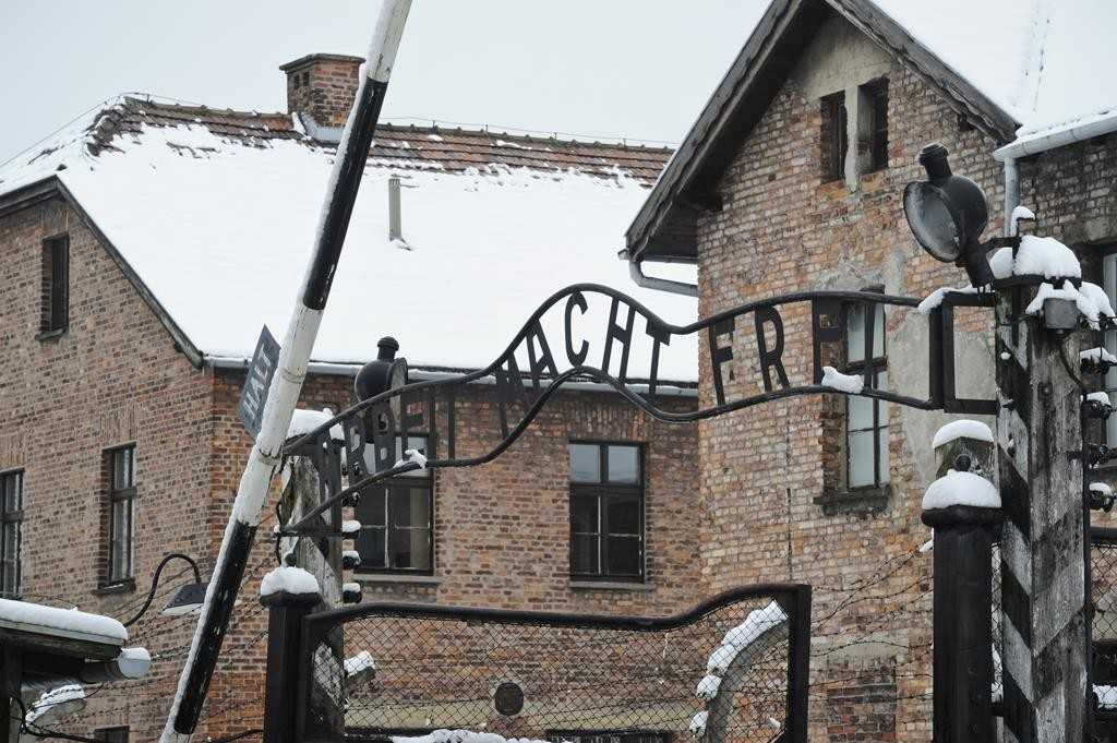 """The """"Arbeit Macht Frei"""" (Work Sets you Free) sign above the entrance gate of the Auschwitz Nazi death camp, is backdropped by detention buildings, in Oswiecim, Poland in this file photo. (AP Photo/Alik Keplicz)"""