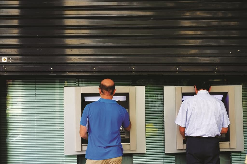 Men use the ATM outside of a closed bank five days before the upcoming referendum, in central Athens, on Tuesday. (AP Photo/Petros Karadjias)