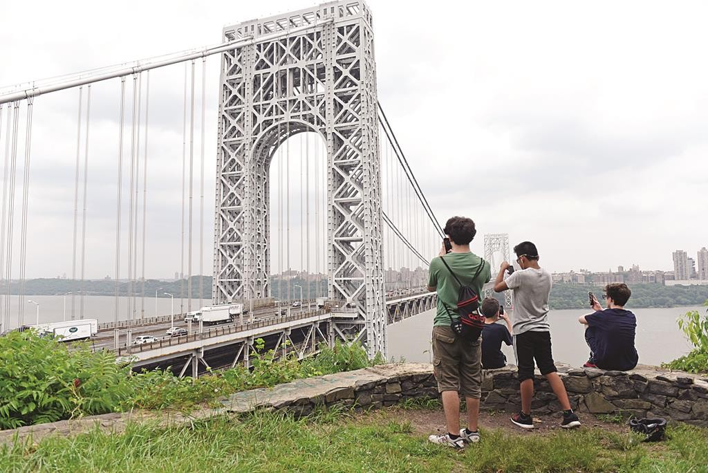 L-R: Teenagers Sam Silber, Adam Levinsohn, Carlos Villanueva and Leuart Ramadani take in the view of the George Washington Bridge from the overlook in Fort Lee, NJ., on a hot and muggy Tuesday afternoon. (Tyson Trish/The Record of Bergen County via AP)